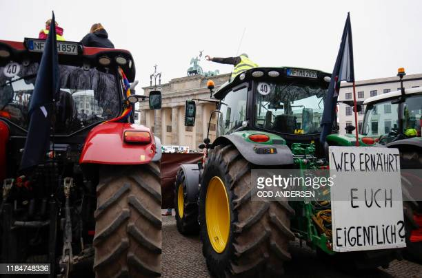 """Farmers sit on their tractors with a placard reading """"Do you know who feeds you ?"""" as they are in position in front of Brandenburg Gate during a..."""