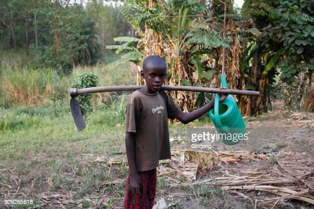 Farmer's son carrying tools Uganda