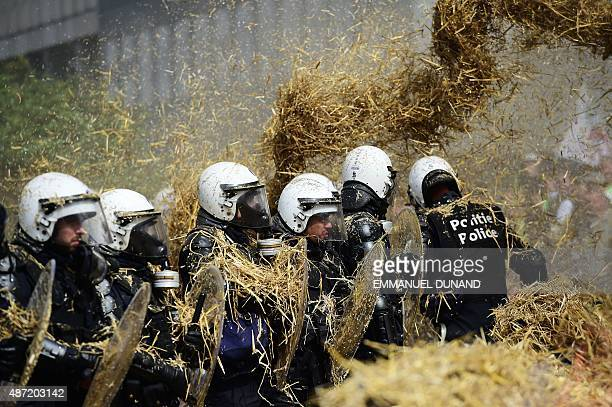 Farmers spread straws on police forces from a combine harvester during a demonstration in front of the European Commission building on September 7 in...
