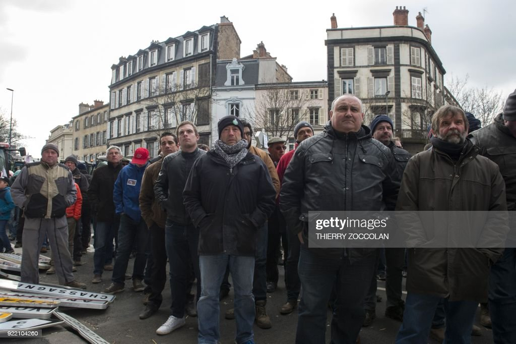 Farmers stand next to road signs during a demonstration called by French trade unions on February 21, 2018 in Clermont-Ferrand to protest against the negotiations between Mercosur and the European Union and the revision of the map of disadvantaged areas through which certain communes receive aid. Negotiators from Mercosur and the European Union are due to resume talks on February 21 after edging closer to a historic trade deal during the last round in Brussels. / AFP PHOTO / Thierry Zoccolan