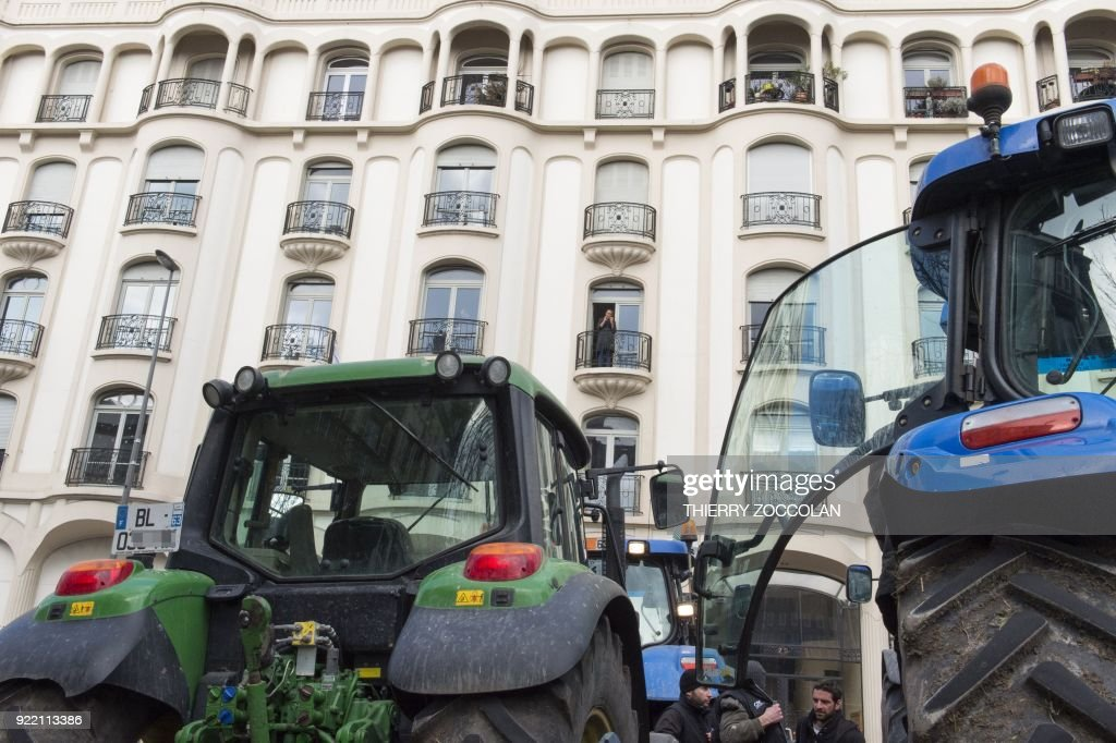 Farmers stand next to tractors during a demonstration called by French trade unions on February 21, 2018 in Clermont-Ferrand to protest against the negotiations between Mercosur and the European Union and the revision of the map of disadvantaged areas through which certain communes receive aid. Negotiators from Mercosur and the European Union are due to resume talks on February 21 after edging closer to a historic trade deal during the last round in Brussels. / AFP PHOTO / Thierry Zoccolan