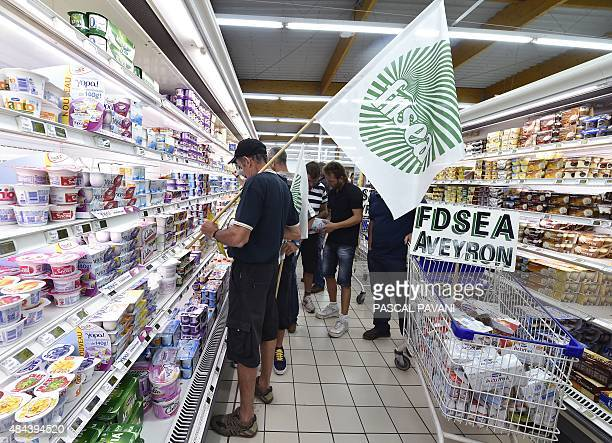 Farmers stick stickers on consummer goods reading in French 'Made with milk sold at loss Farmers strangled Savencia fattened' as part of a prices and...