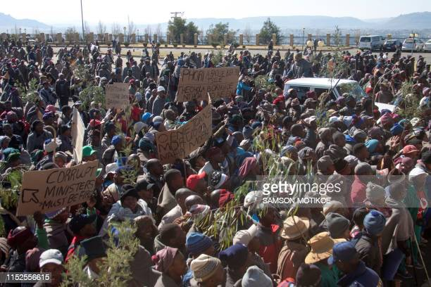 Farmers take part in a march to parliament as placards read 'Phori must be castrated' 'How is the nations's economy now Moeketsi Majoro' 'Corrupt...