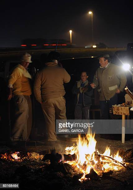 Farmers talk next to a bonfire in the side of the route 191 near San Pedro in the province of Buenos Aires on October 7 during a vigil in the fifth...
