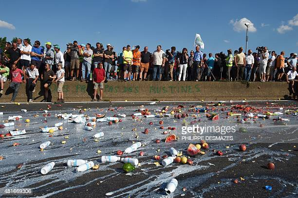 Farmers throw bricks of milk and fruits on the ground as part of a demonstration against the market prices of their products on July 23 2015 in Lyon...