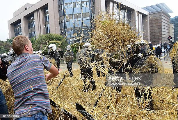 Farmers throw straws on police forces during a demonstration in front of the European Commission building on September 7 in Brussels as European...