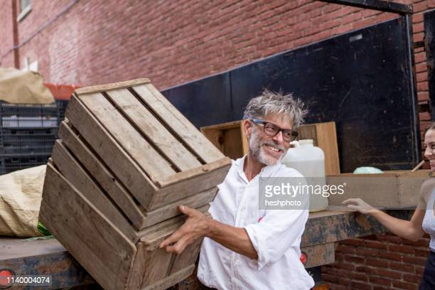 farmers unloading crates of organic food for store - heshphoto stock pictures, royalty-free photos & images