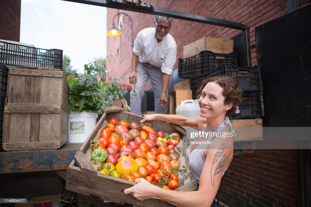 Farmers unloading crates of organic tomatoes outside grocery store : Stock Photo