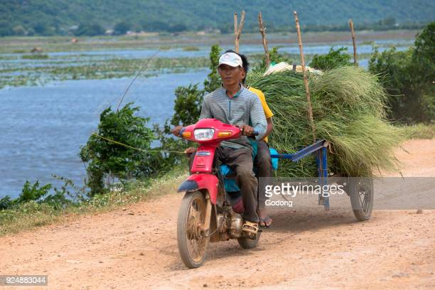 Farmers using a scooter and cart to carry goods Battambang Cambodia