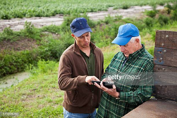 Farmers using digital tablet on potato farm