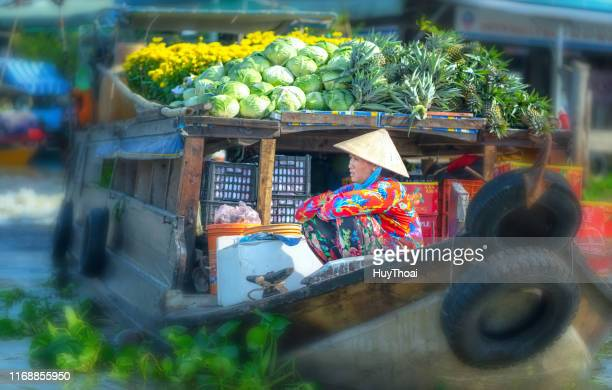 farmers wait for customers on the boat - floating market stock photos and pictures