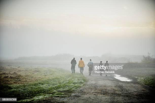 Farmers walking on road to harvest in field