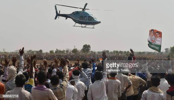 Farmers waves at Congress president Rahul Gandhi as he leaves in helicopter after addressing 'Kisan Samriddhi Sankalp' rally in Pipliya Mandi at...