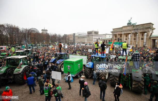 Farmers with their tractors and protestors gather in front of Brandenburg Gate during a protest on November 26, 2019 in Berlin against the German...