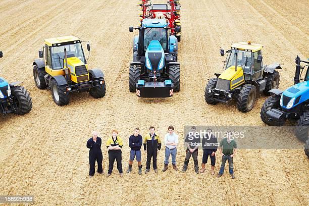 Farmers with tractors in crop field