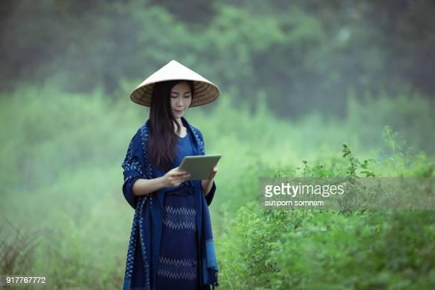 Farmers women use a tablet to work in garden
