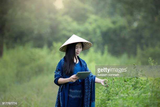 Farmers women use a tablet to work in indigo plant
