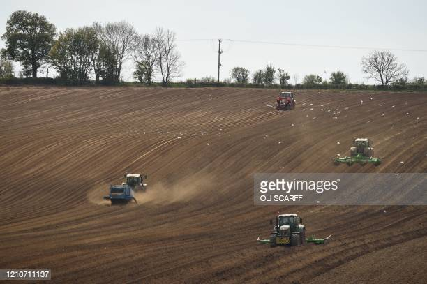 Farmers work in a field with vehicles near Pontefract, northern England, on April 23, 2020 as life continues under lockdown in the UK to help halt...