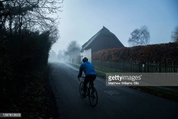Farmhouse and bicyclist on road in mist, Cotswald, UK.