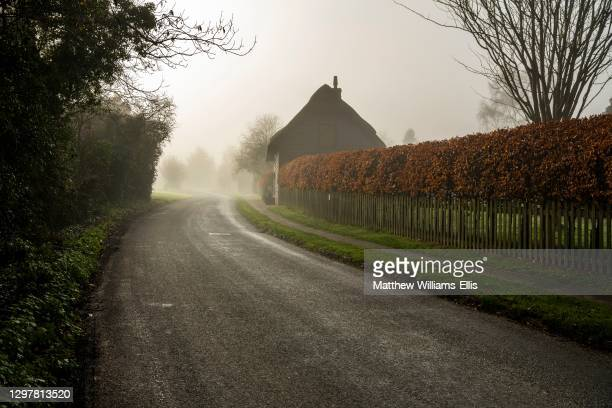 Farmhouse and road in mist, Cotswald, UK.