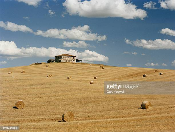farmhouse in a field with hay bales - yeowell stock photos and pictures