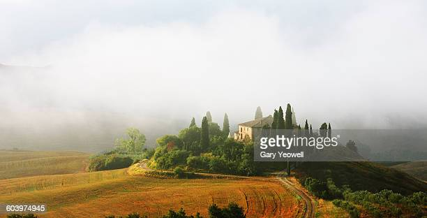 Farmhouse in misty Tuscan landscape