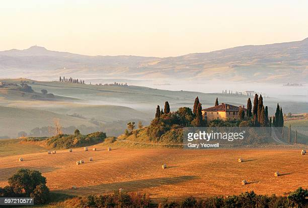 Farmhouse in rolling Tuscan landscape at dawn