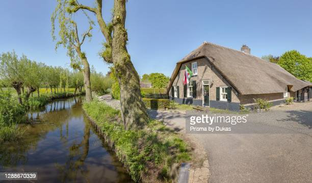 Farmhouse with thatched roof at a tree lined stream, Noordeloos, Zuid-Holland.