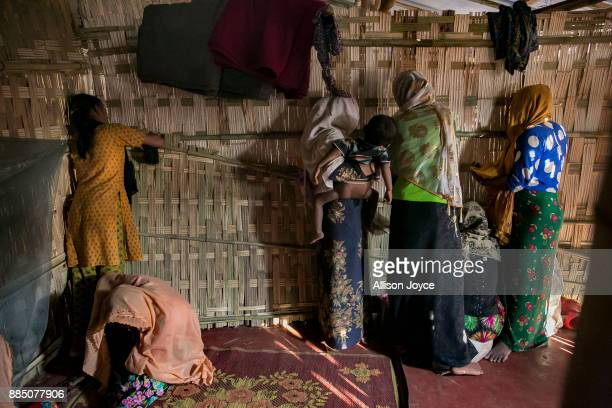 COX'S BAZAR BANGLADESH NOVEMBER 27 Farmina Begum sits on the ground while women peer through the wall separating men from women on the day of the...