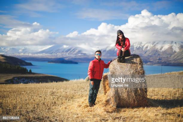 farming and harvest in new zealand- couple celebrating hay bales - south island new zealand stock pictures, royalty-free photos & images
