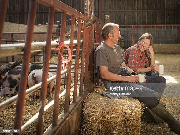 Farming couple taking a break in barn
