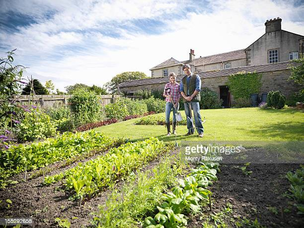Farming couple tending to organic  vegetables in garden with farm house in background