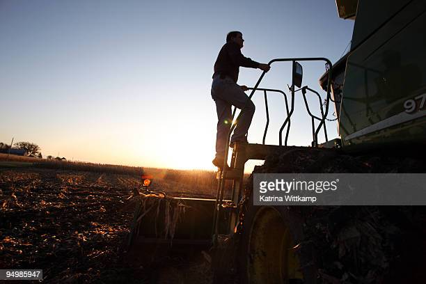 farming stepping onto his combine. - combine harvester stock pictures, royalty-free photos & images