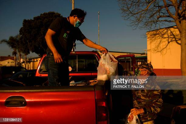 Farmworker and United Farm Workers member Guillermo Garcia gives a bag of groceries to a retiree following a community outreach meeting about...