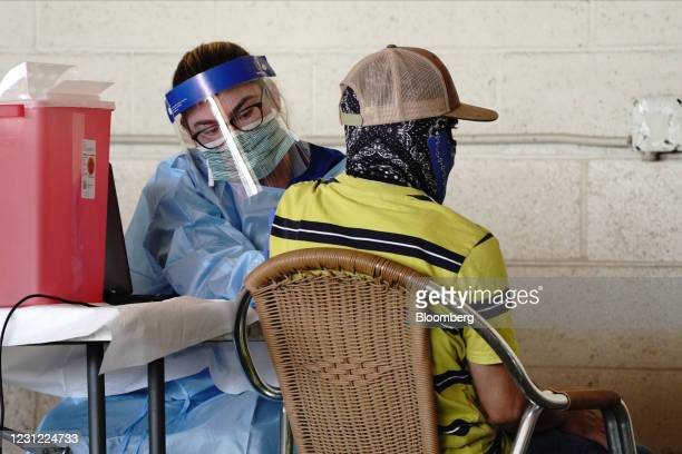 Farmworker receives a dose of the Pfizer-BioNTech Covid-19 vaccine at a vaccination clinic organized by Riverside County and Desert Healthcare...