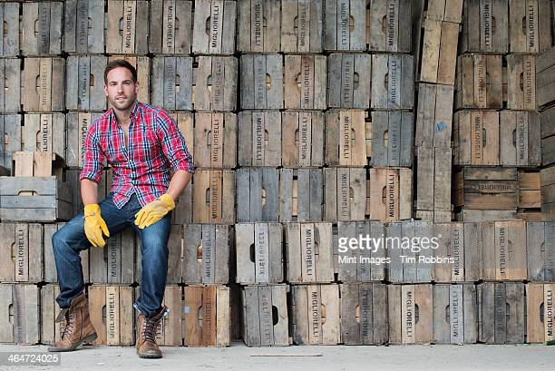 A farmyard. A stack of traditional wooden crates for packing fruit and vegetables. A man sitting on a packing case.