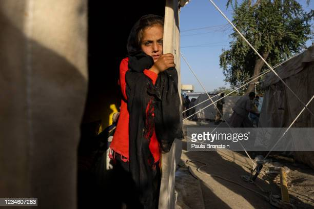 Farnaz, age 7, from Tahar stands by a tent as displaced Afghans arrive at a makeshift camp from the northern provinces desperately leaving their...