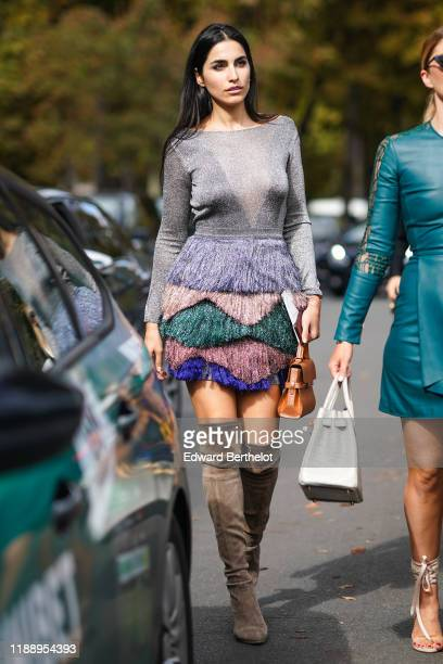 Farnoush Hamidian wears a silver glitter mesh dress with colored ruffles a brown bag brown suede high boots outside Elie Saab during Paris Fashion...