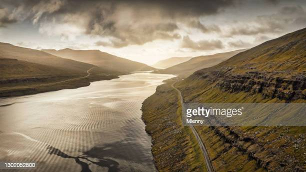 faroe islands coastal fjord road between streymoy and eysturoy island sunset panorama - mlenny stock pictures, royalty-free photos & images