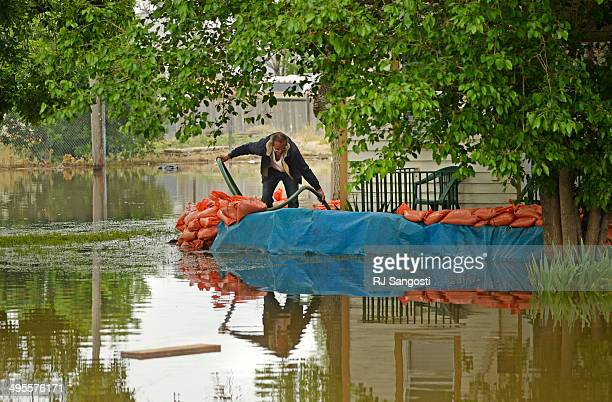 Farr West checks on his sump pump outside his home in Greeley that is flooded by rising water along the Poudre River June 4 2014 A flood warning for...
