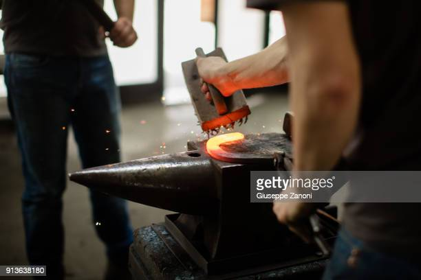 farrier forging horseshoe on anvil - horseshoe bat stock pictures, royalty-free photos & images