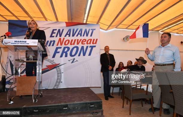 Farright Front National party leader Marine Le Pen delivers a speech at the tribune near a man holding a French flag during a meeting on October 08...
