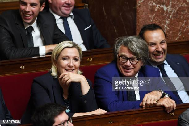 Farright Front National party members of parliament Marine Le Pen and Gilbert Collard laugh as they attend a session of questions to the government...