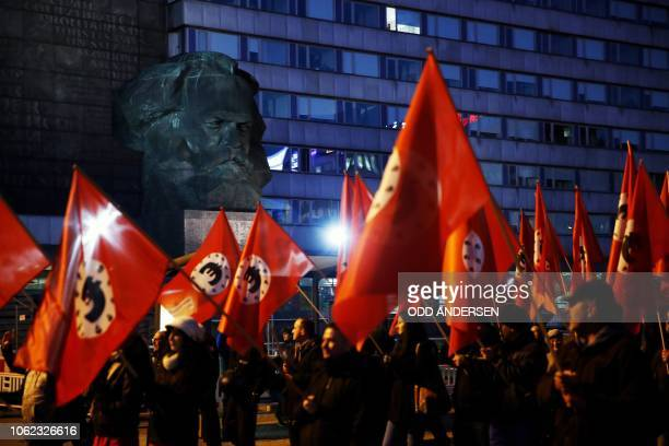 Farright protesters march past the statue of Karl Marx in the eastern Germany city of Chemnitz on the sidelines of a visit of German Chancellor on...