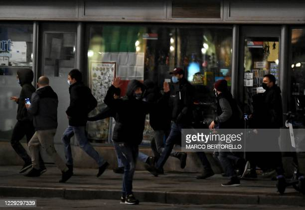 Far-rigth activists run during a protest against the government restriction measures to curb the spread of COVID-19, in downtown Turin, on October 26...