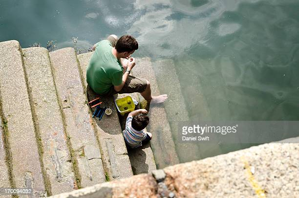 Farther teaching son to catch crabs on harbour steps, Tenby harbour in Pembrokeshire, Wales