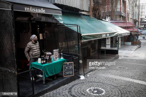 Faruk Ugur waits for customers while selling hot wine at the entrance to his closed restaurant in the Kadikoy district on February 23, 2021 in...