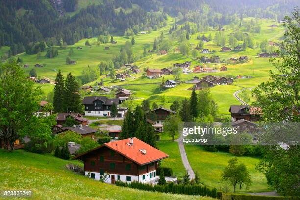 fary tale landscape: above idyllic grindelwald alpine village cityscape valley and meadows, dramatic swiss snowcapped wetterhorn alps, idyllic countryside, bernese oberland,swiss alps, switzerland - valais canton stock pictures, royalty-free photos & images