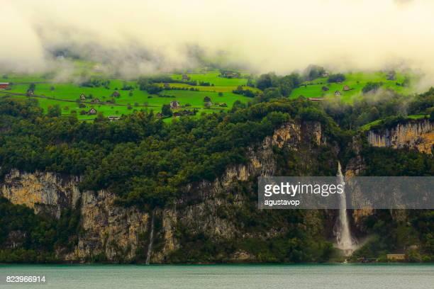 Fary tale landscape: waterfall cascade cliff into lake - idyllic alpine chalets, farms, valley and meadows, dramatic swiss alps, idyllic countryside, Bernese Oberland,Swiss Alps, Switzerland