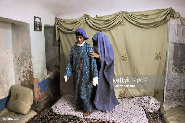 Farzana is helped to stand up by her mother at home as they prepare to go to a private clinic in Herat Afghanistan August 5 2010 Farzana tried to...